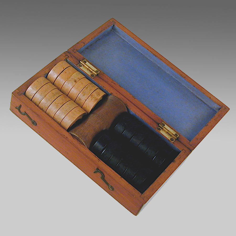 Antique mahogany boxed set of boxwood and ebony draughtsmen